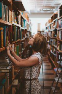 djevojka u potrazi za adekvatnom literaturom u knjiznici